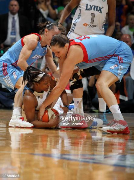 Monica Wright of the Minnesota Lynx guards the ball against Alison Bales and Coco Miller of the Atlanta Dream in Game One of the 2011 WNBA Finals on...