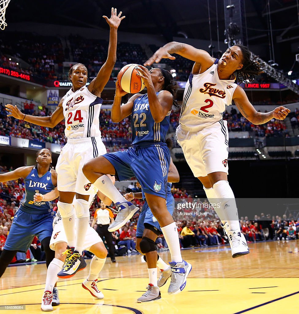 Monica Wright #22 of the Minnesota Lynx shoots the ball as Tamika Catchings #24 and Erlana Larkins #2 of the Indiana Fever defends during Game Four of the 2012 WNBA Finals on October 21, 2012 at Bankers Life Fieldhouse in Indianapolis, Indiana.