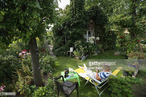 Monika who preferred not to reveal her last name knits on a lawnchair next to the ivycovered cottage in the garden she and her husband Mario have...