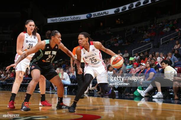 Monique Currie of the Washington Mystics drives against Alex Montgomery of the New York Liberty at the Verizon Center on May 30 2014 in Washington DC...
