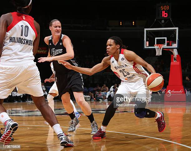 Monique Currie of the Washington Mystics drives against Cathrine Kraayeveld of the San Antonio Silver Stars at the Verizon Center on July 16 2012 in...