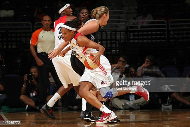 Monique Currie of the Washington Mystics drives against Jayne Appel of the San Antonio Silver Stars at the Verizon Center on July 6 2012 in...