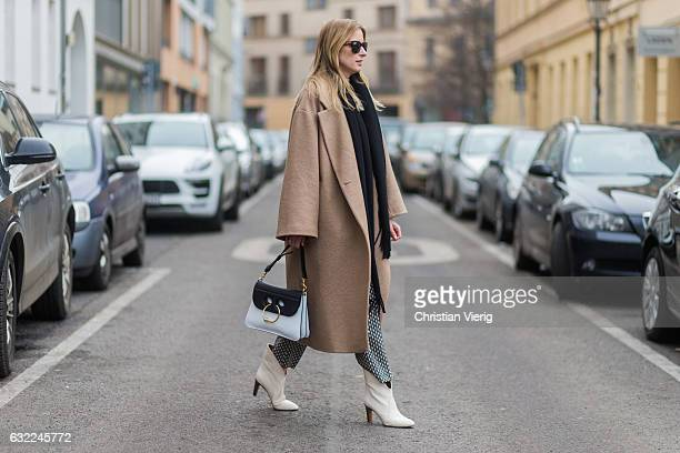 Monique Romanowski wearing a JW Anderson bag scarf Acne Studios Chloe boots HM Premium coat HM pants during the MercedesBenz Fashion Week Berlin A/W...