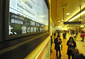 A monitor announcing train service delay due to the snow fall is displayed at the JR Tachikawa Station on January 18 2016 in Tachikawa Tokyo Japan A...