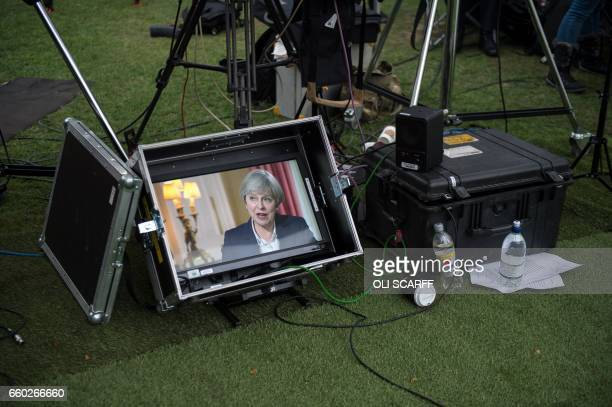 A monitor showing an interview with British Prime Minister Theresa May is positioned in a television news crew's temporary outside studio near the...