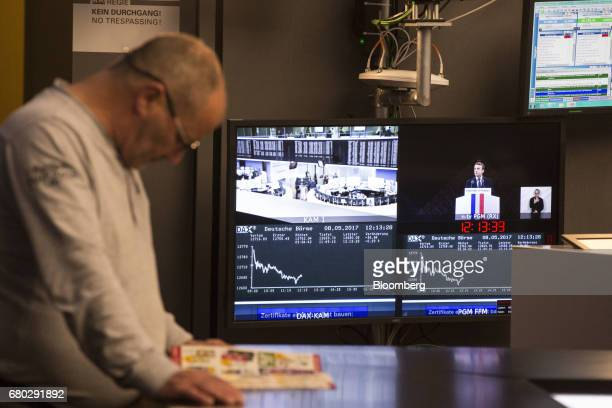 A monitor shows the DAX Index curve and France's presidentelect Emmanuel Macron inside the Frankfurt Stock Exchange in Frankfurt Germany on Monday...
