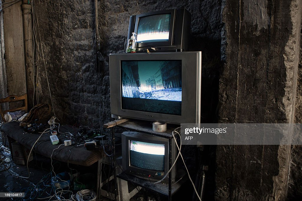 TV monitors broadcast the live feed from a camera situated on an electrical car (unseen), used by rebel fighters for monitoring Syrian government forces in the Bab al-Nasr district of Aleppo's Old City, on January 7, 2012. Syria's domestic opposition snubbed a call to dialogue from President Bashar al-Assad, as NATO powers challenged the leader's defiant grip on power and dispatched Patriot missile batteries to neighbouring Turkey.