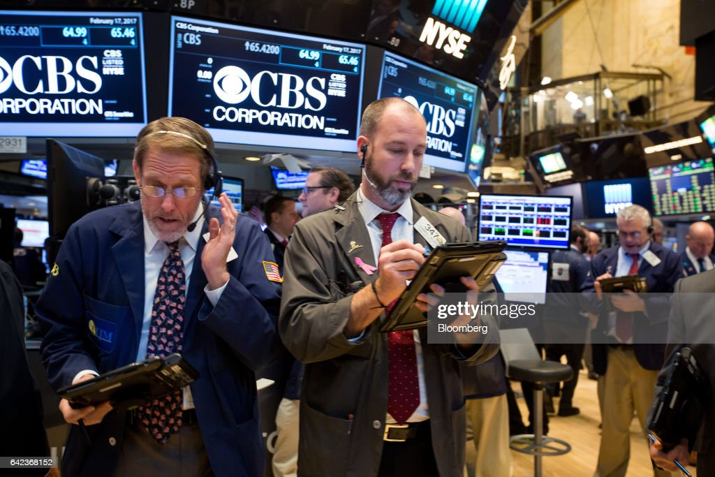 Monitors Display CBS Corp. Signage While Traders Work On The Floor Of The  New York