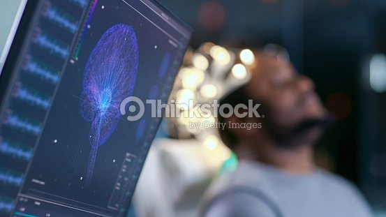 Monitors Show EEG Reading and Graphical Brain Model. In the Background Laboratory Man Wearing Brainwave Scanning Headset Sits in a Chair with Closed Eyes. In the Modern Brain Study Research Laboratory : Stock Photo