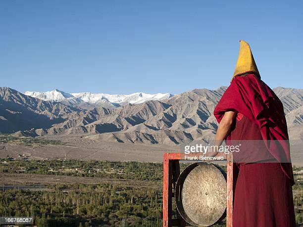 THIKSEY JAMMU KASHMIR INDIA Monk calling for the morning prayers from the rooftop of Thikse Gompa