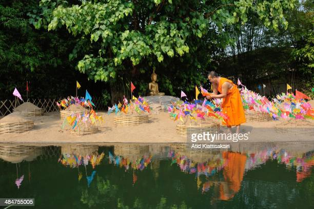 A monk decorates sand chedis with colorful flags at Wat Phun On during the Songkran festival The Songkran festival which is the traditional Thai new...