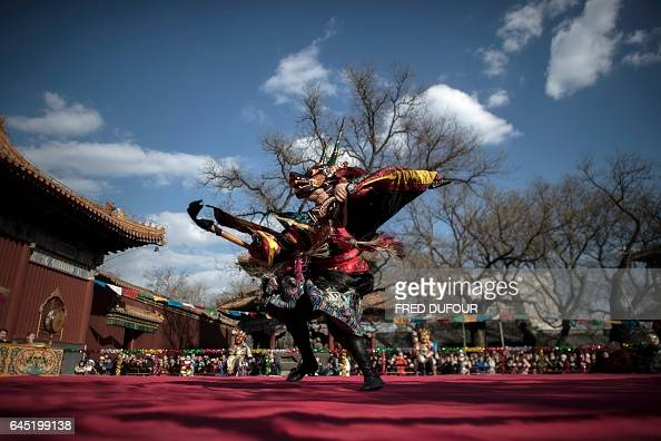 TOPSHOT A monk dressed as a Tibetan Buddhism character performs a dance for the Beating Ghost festival at the Yonghe Temple also known as the Lama...
