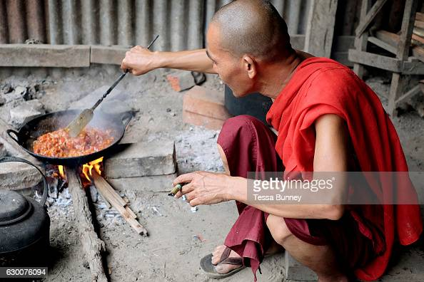 A monk makes breakfast whilst smoking a cheroot at Shwe Pan Myaing Monastery in Mandalay on 25th May 2016 in Myanmar