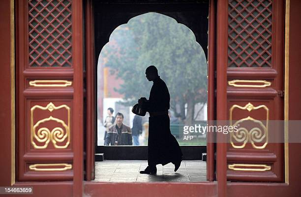 A monk makes his way through a hall with a kettle in his hand at the Yonghegong Lama temple in Beijing in Beijing on October 24 2012 China's...