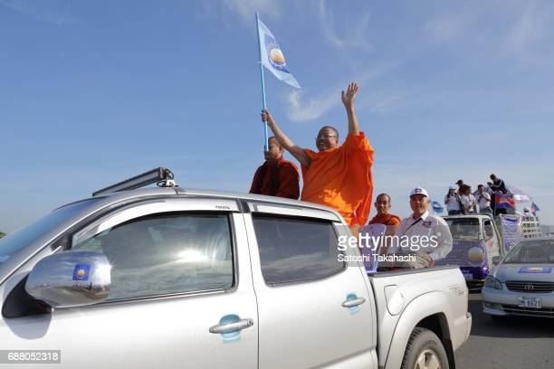 A monk of supporter of the opposition Cambodia National Rescue Party holds a CNRP flag during a march on the first day of campaigning for the commune...