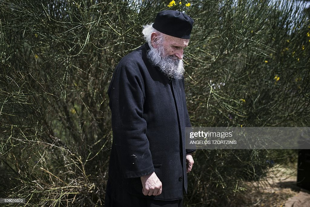 A monk of the Greek Orthodox Church attends the ceremony marking the Apokathelosis, the removal of Christ's dead body from the Cross, which forms a key part of Orthodox Easter, in a ceremony at the Church of the Dormition of the Virgin in Penteli, north Athens on April 29, 2016 Millions of Greeks flock to churches around the country this week to celebrate Easter, the country's foremost religious celebration. / AFP / ANGELOS