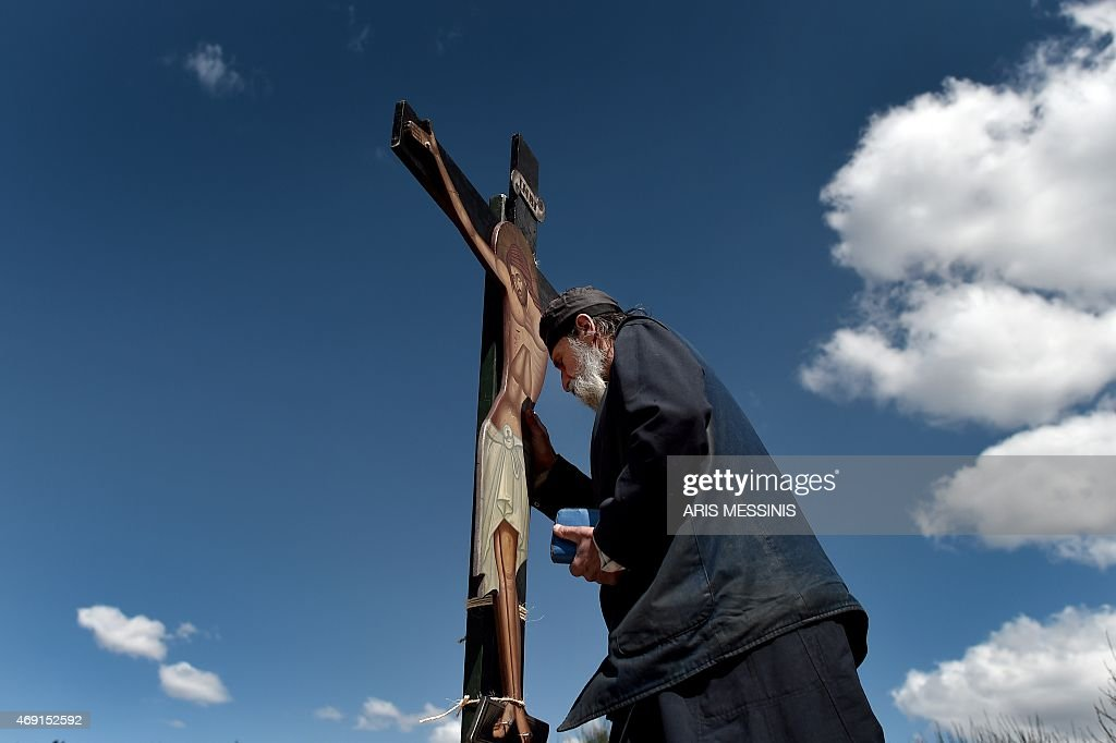 A monk of the Greek Orthodox Church stands in front of an image of Jesus crucified during the ceremony marking the Apokathelosis the removal of...