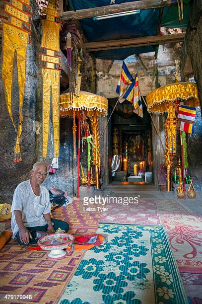 A monk offering blessings inside the main alter hall of Phnom Chisor a temple built in the 11th century by the Khmer Empire king Suryavarman A...