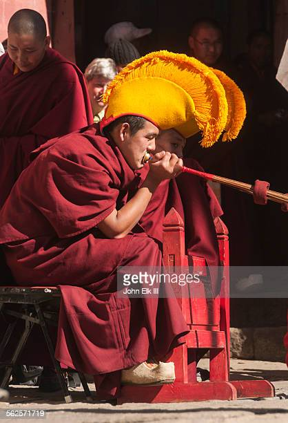 Monk playing giant trumpet