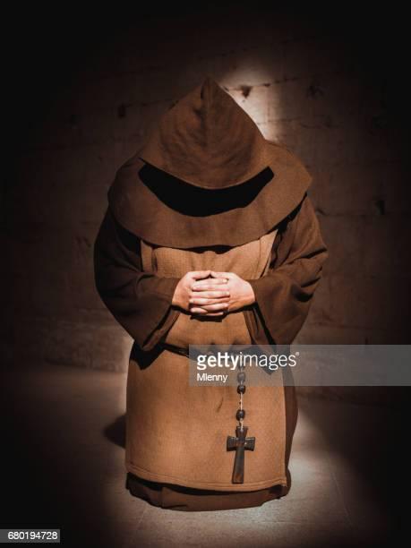 Monje orando de rodillas en la Catedral