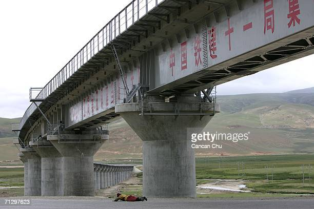 A monk prays near a railroad bridge of the QinghaiTibet Railway as they make their pilgrimage to Lhasa the sacred Buddhist center for pilgrims on...