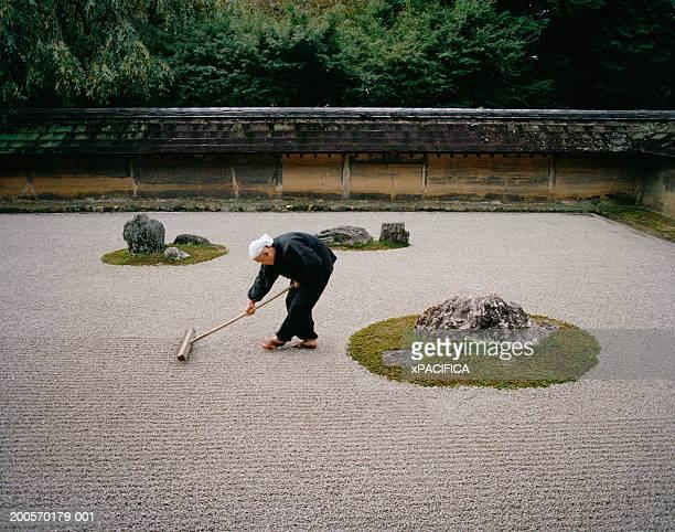 Monk raking rock garden of Ryoanji Temple, Japan