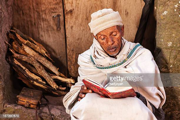 Monk reading the holy book near one of Lalibela's churches