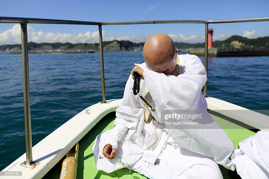 A monk shed tears after holding memorial ceremony at the sea near Ena port on September 11, 2012 in Iwaki, Fukushima, Japan. 18 months on, still 2,814 people are missing and 340,000 people are forced to live at temporary housing.