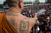 Monk spray holy water on the crowd helping by a water pipe in Nakhon Chai Si district Thailand about 50 km west of Bangkok on March 7 2015 Thousands...