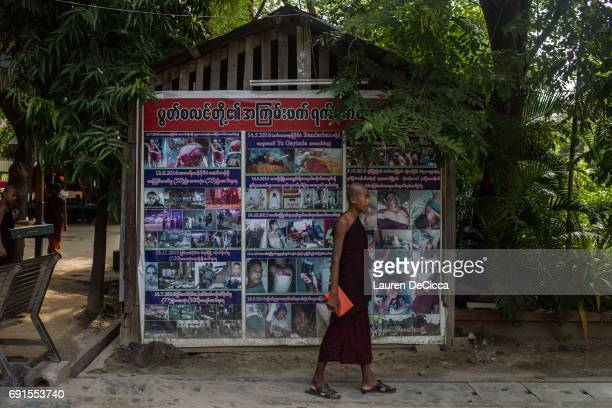 A monk stands infront of a poster showing alledged abuses made by Muslims on the Buddhist community another type of propaganda spread by Wirathu and...