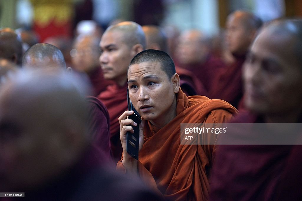 A monk talks on his mobile phone during a meeting of Buddhist monks at a monastery outside Yangon on June 27, 2013. Myanmar was due to reveal winners of two licences to provide mobile coverage in a country where less than 10 percent of the population has access to a telephone. AFP PHOTO / Ye Aung THU