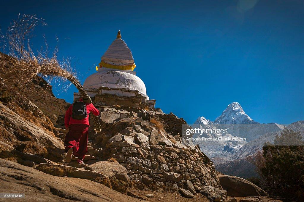 A monk walk pass stupa on view of Ama Dablam mountain peak background