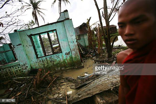 A monk walks by a destroyed house at the isolated village of Mingala Taungtan on May 20 2008 in the Ayeyarwaddy delta Myanmar It has been estimated...