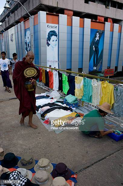 A monk walks past street vendors on a pedestrian overpass with a building sporting fashion model advertising posters behind