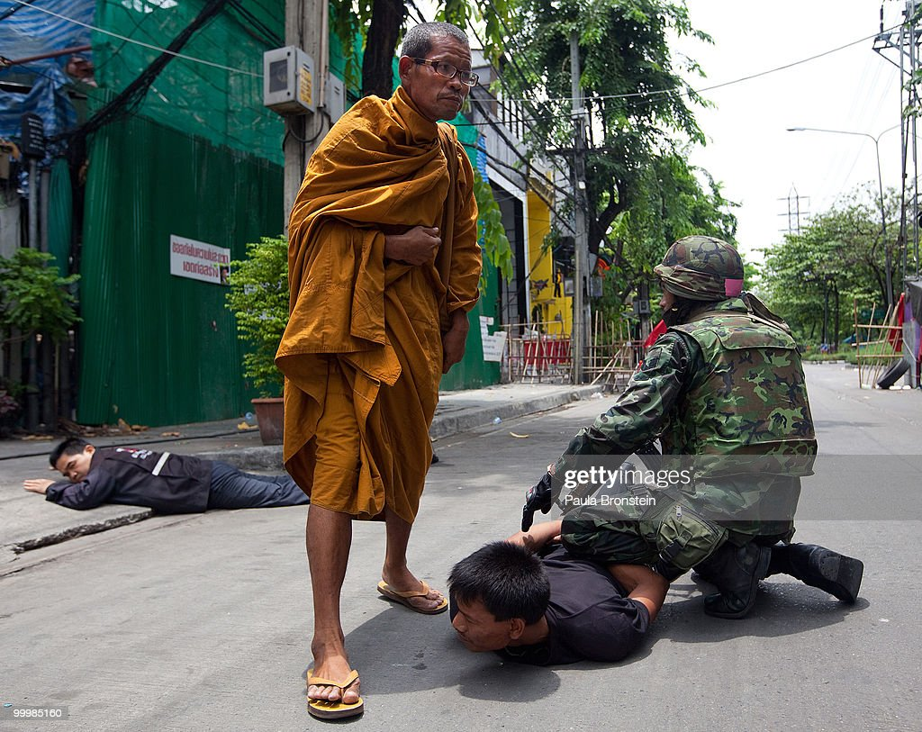 A monk watches as a red shirt anti-government protester surrenders to the military inside the red shirt camp on May 19, 2010 in Bangkok, Thailand. At least 5 people are reported to have died as government forces sought to overrun barricades raised in and around the city centre by anti-government protestors. Red-shirt leaders have now surrendered, ending their blockade in the aftermath of a sixth day of violence, leaving the army in control and a night time curfew to be imposed.
