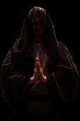 Vertical shot of a monk with a hood on his head praying on black background