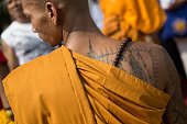 Monk with religious tattoo on his back is pictured inside the main temple of Wat Bang Phra in Nakhon Chai Si district Thailand about 50 km west of...