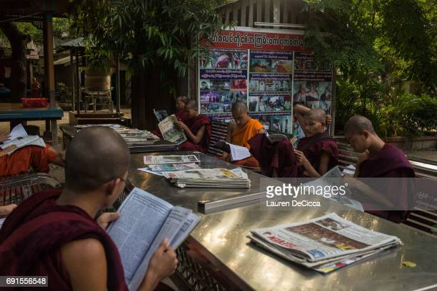 Monks at the Masoeyein Monastery read newspapers in front of the temple on May 31 2017 in Mandalay Burma Many of the government run newspapers aid in...
