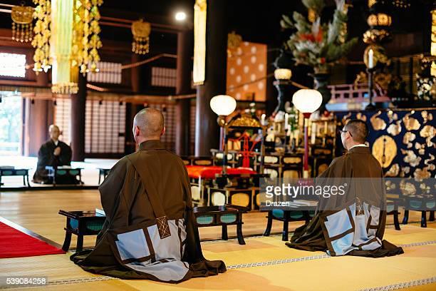 Monks during prayer in Buddhist shrine in Kyoto
