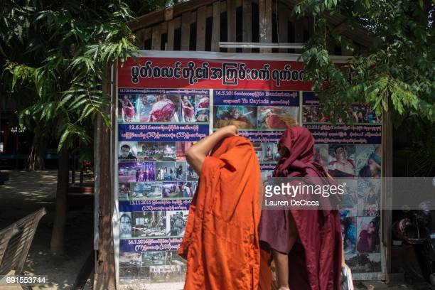 Monks look at a poster showing alledged abuses made by Muslims on the Buddhist community another type of propaganda spread by Wirathu and his...