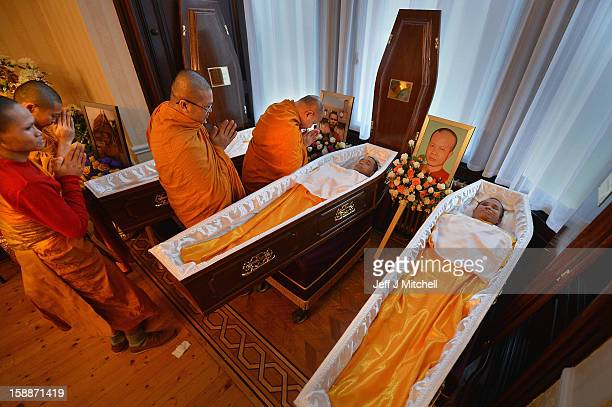 Monks pary over the open coffins at a service of remembrance for three Thai Buddhist Monks who died in a car crash on Christmas Eve at Oakvale...