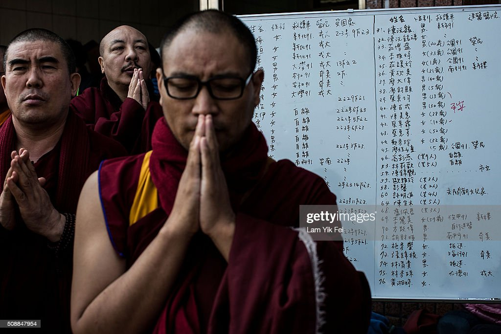 Monks pray near a list of the patients near a collapsed building on February 7, 2016 in Tainan, Taiwan. A magnitude 6.4 earthquake hit southern Taiwan early Saturday, toppling several buildings, killing at least fourteen people and leaving over one hundred missing in Tainan.