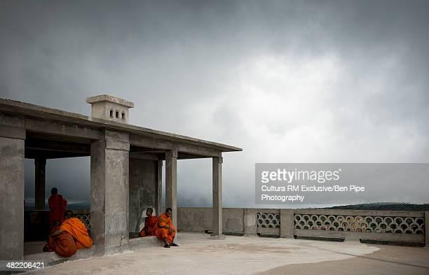 Monks sitting outside building, Bokor national park, Kampot, Cambodia