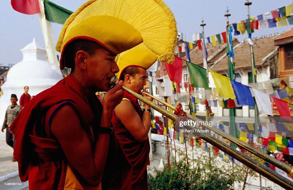 Monks sounding long horns to commence Losar (Tibetan New Year) celebrations at Bodhnath Stupa.
