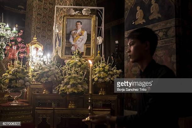 A monk's volunteer gives a candle to a monk in front of His Majesty King Maha Vajiralongkorn Bodindradebayavarangkun at Wat Pathum Wanaram during his...