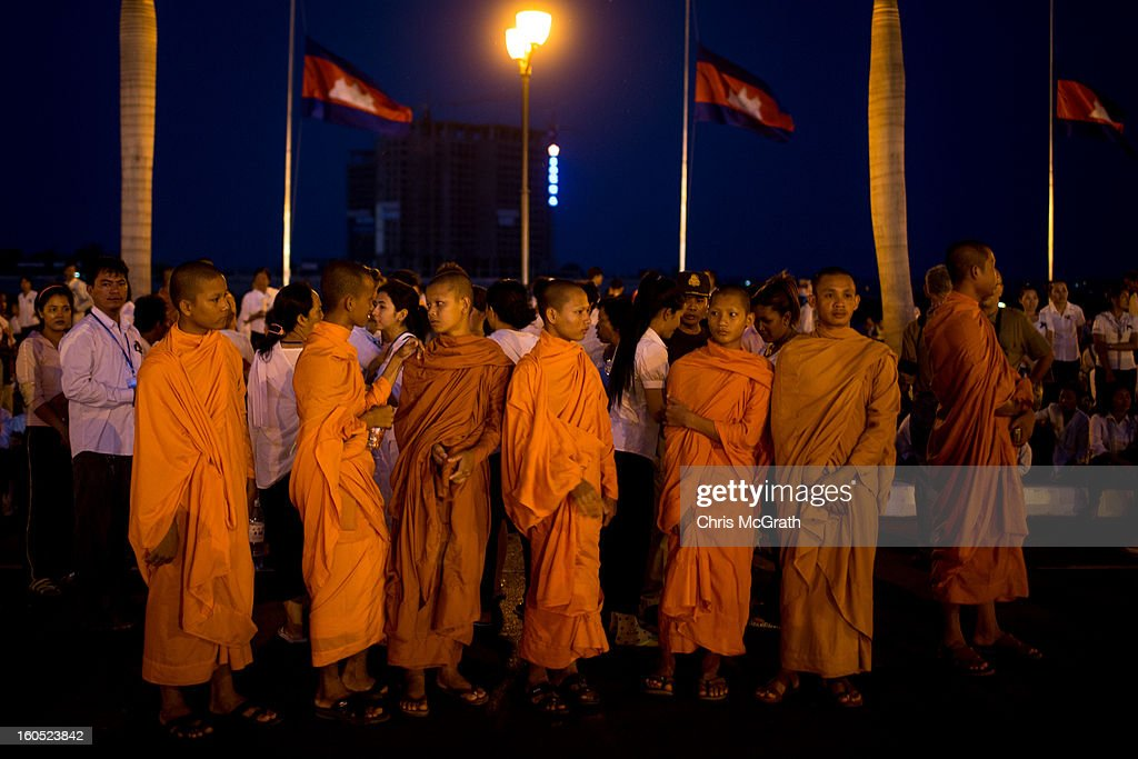 Monks wait on a roadside outside the Royal Palace for a ceremony involving King Norodom Sihamoni to finish before being able to pay their respects to former King Norodom Sihanouk on February 2, 2013 in Phnom Penh, Cambodia. The former kings coffin was transported to the cremation site yesterday after being paraded through the capital in a lavish funeral procession. The cremation will take place on Monday the 4th of February, the funeral pyre will be lit by his wife and son King Norodom Sihamoni.