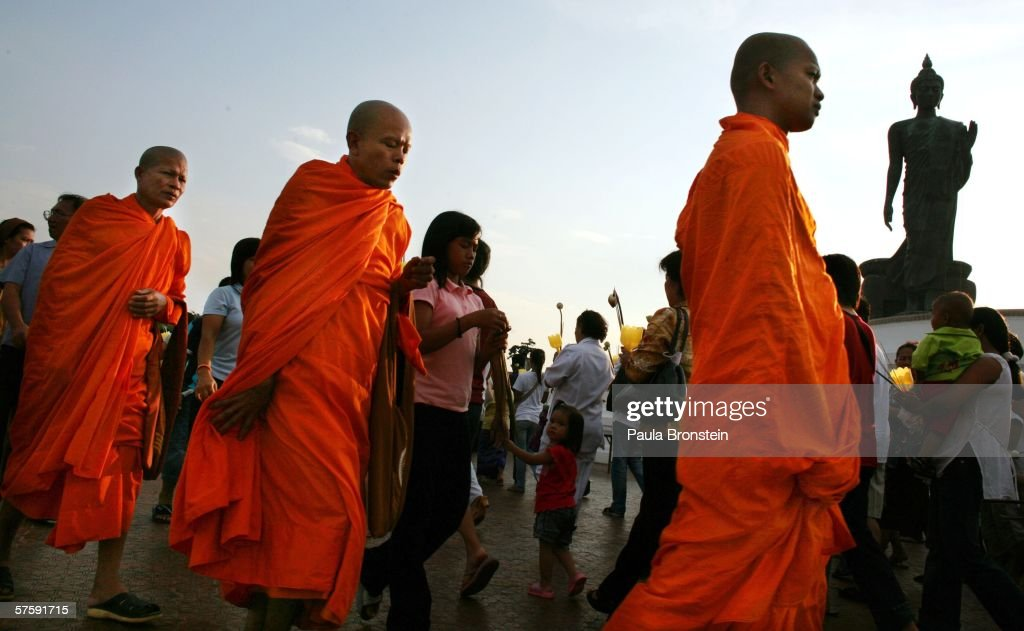 Monks walk around the Buddha statue at sunset at Buddhist Park on Visakha Puja Day May 12 2006 in Thailand Visakha Puja day is the day that Lord...