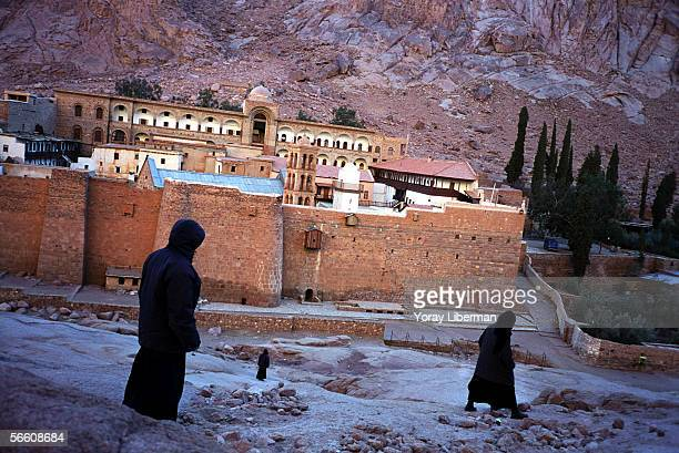 Monks walk next to Saint Catherine Monastery on January 01 2004 in Sinai Desert Egypt Saint Catherine monastery in Sinai desert is an attractive...