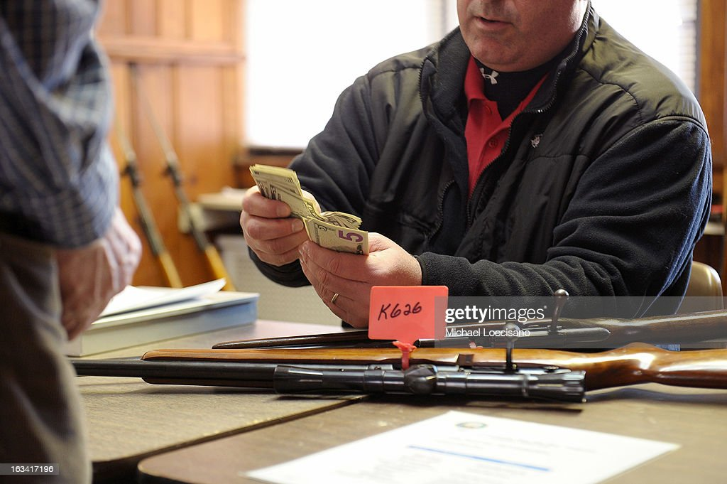 Monmouth County Prosecutor's Office Lieutenant Jay Clark exchanges cash for firearms during a gun buyback program on March 9, 2013 in Keansburg, New Jersey. In a national effort to curb gun violence, the NJ Attorney General's Office in cooperation with the Monmouth County Prosecutor's Office held an anonymous buyback program where every gun turned in is to be melted down.