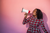 Young black woman standing in front of pink background turns head to side yelling into a megaphone.
